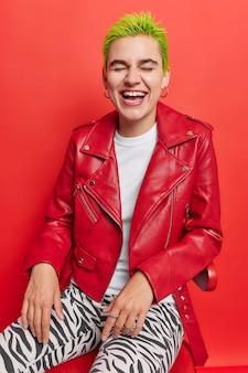 短い染められた緑の髪の少女が笑うのは、革のジャケットに身を包んだ並外れた外観と、赤の椅子にポーズをとるレギンスが楽しいです。