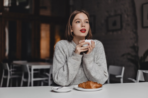 Girl with short hair and red lipstick dressed in warm sweater enjoying tea with croissant in cozy cafe.