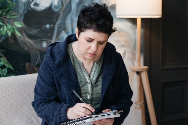 短い髪の少女は、ノートに書き込み、電話をかけ、自宅から離れた場所で仕事をします。