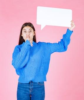 Девушка с знаменем пузыря речи знака показывая безмолвный знак на розовом.