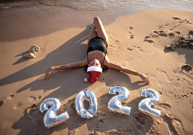 Ragazza con palloncini d'argento sotto forma di numeri per il prossimo anno vicino al mare