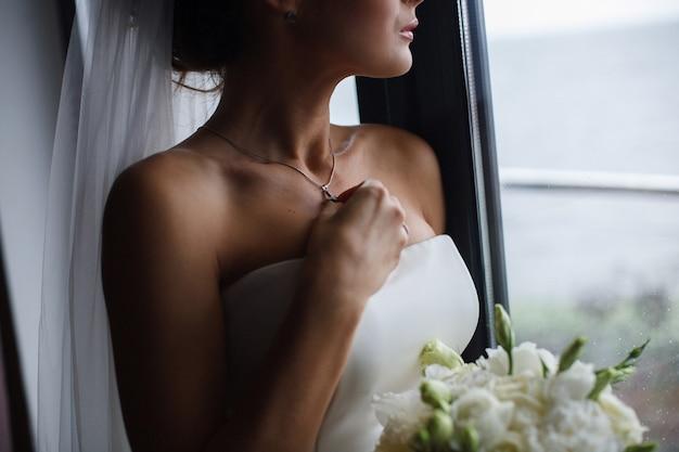 彼女の首に銀の鎖を持つ少女をクローズアップ。美しい花嫁の肖像画は、首に宝石の装飾を修正します。花嫁は装飾を修正します。女性の首のペンダント。結婚式の日