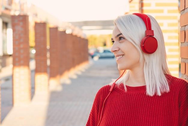 銀の髪と赤いヘッドフォンの笑顔の女の子。街の柱に寄りかかって。