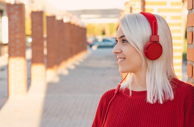 Girl with silver hair listening to music with red headphones. leaning on a column in the city. dressed in a red sweater.