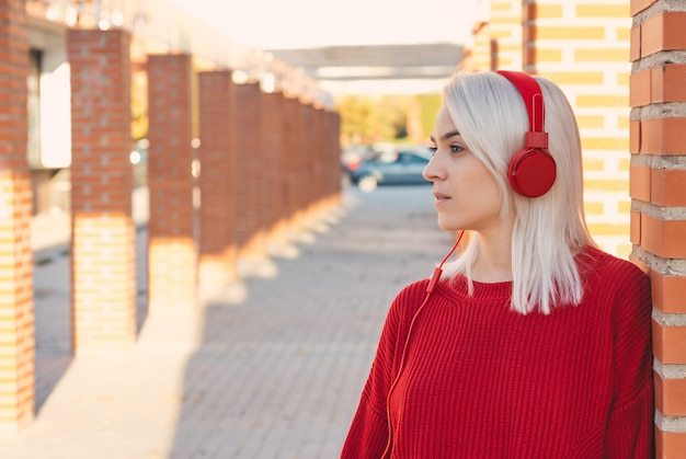 Girl with silver hair listening to music with red headphones. leaning on a column in the city.