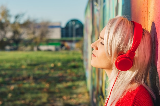 Girl with silver hair listening to music with red headphones. leaning on a graffiti wall. dressed in a red sweater.