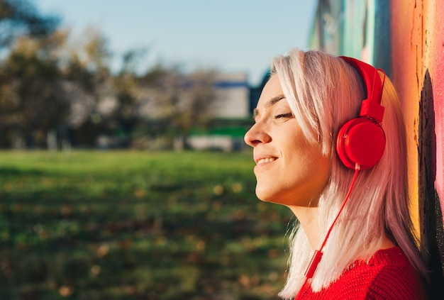 Girl with silver hair listening to music with red headphones. leaning on a graffiti wall.