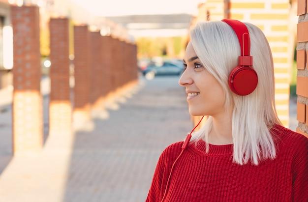 赤いヘッドホンで音楽を聴いている銀髪の少女。街の柱に寄りかかって。赤いセーターを着ています。