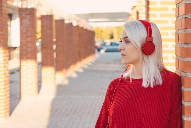 赤いヘッドホンで音楽を聴いている銀髪の少女。街の柱に寄りかかって。