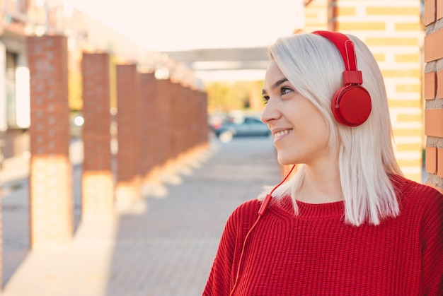 Girl with silver hair and red headphones smiling. leaning on a column in the city.