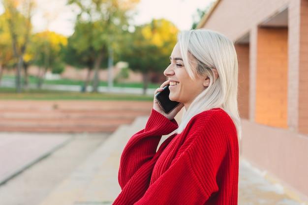 앉아서 그녀의 전화로 말하는 은색 머리를 가진 소녀. 빨간 스웨터를 입고.