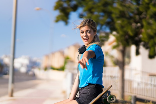 Girl with skate at outdoors surprised and pointing front
