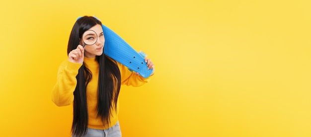 Girl with a skateboard and a magnifier over yellow