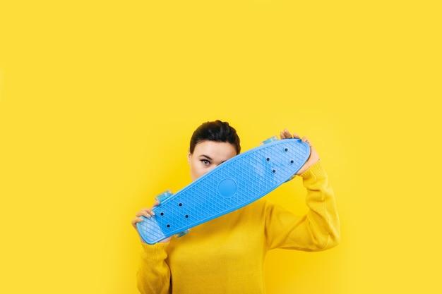 黄色の空間にスケートボードを持つ少女