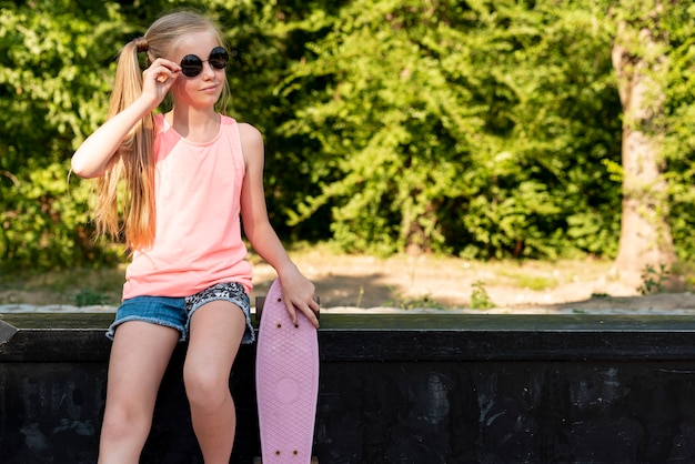 Girl with skateboard sitting on bench