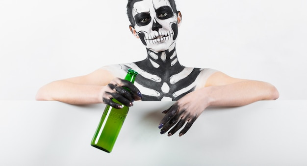 Girl with skeleton makeup hold green glass bottle