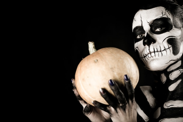 Girl with skeleton makeup holds a pumpkin
