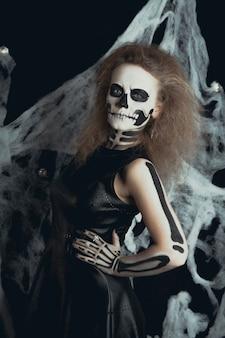 Девушка с макияжем скелета позирует в паутине