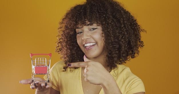 작은 쇼핑 카드와 함께 소녀입니다. 쇼핑 컨셉에서 웃고 춤추는 곱슬머리 여자. 미니어처 카트를 가진 젊은 여자. 전자 상거래 및 비즈니스. 쇼핑카. 여자 구매자입니다. 노란색 배경입니다.