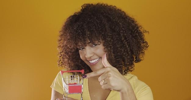 작은 쇼핑 카드를 가진 소녀 쇼핑 개념에서 곱슬 머리 여자 미소와 춤