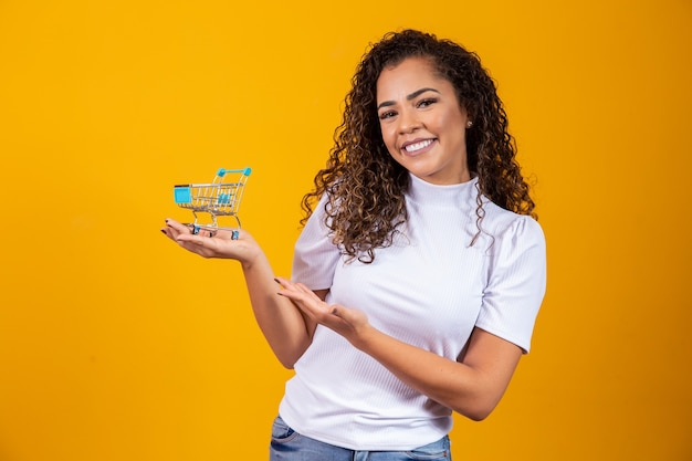 Girl with small shopping card. smiling and dancing curly hair woman in shopping concept. young woman with a miniature cart. e-commerce and business. shopping car. woman shopper. yellow background.