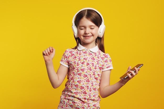 Девушка со смартфоном и белыми наушниками слушает музыку и танцует