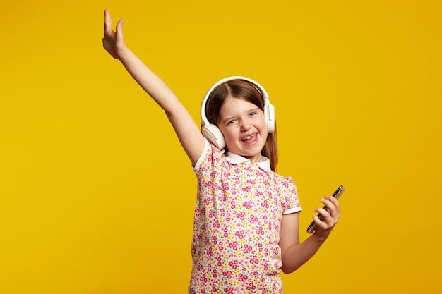 Девушка со смартфоном и белыми наушниками поднимает руку, празднуя победу