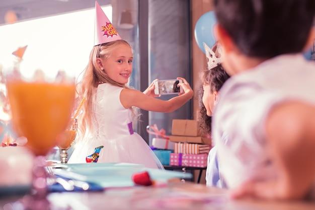 スマートフォンを持つ少女。フレンドリーな長髪の女の子が笑顔でゲストに頭を向けながら自分撮りをしている