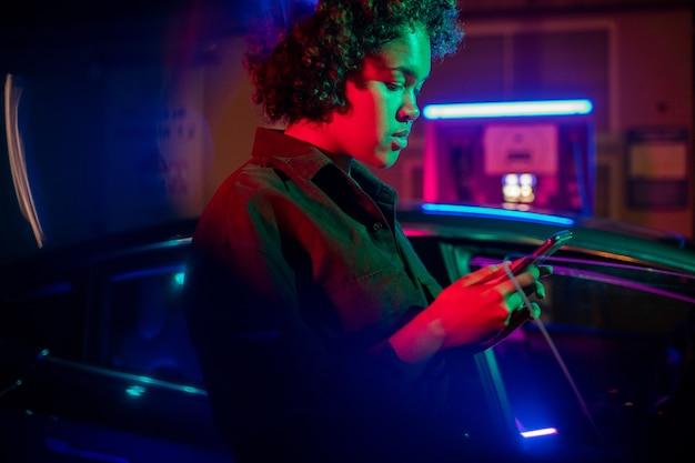 Девушка со смартфоном платит за зарядку электромобиля