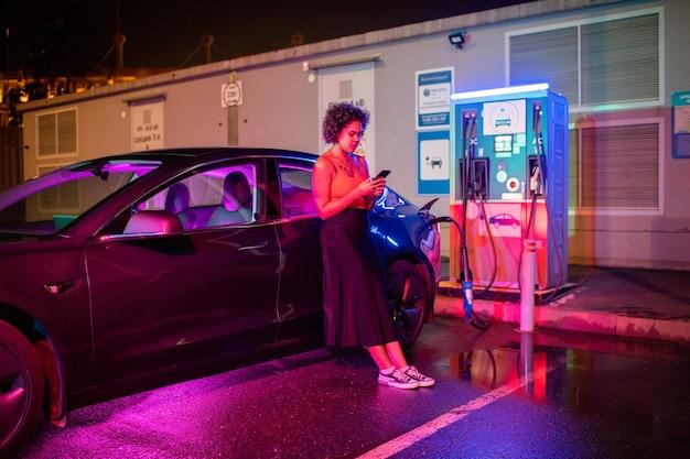 Девушка со смартфоном, стоя на мокром асфальте на электромобиле