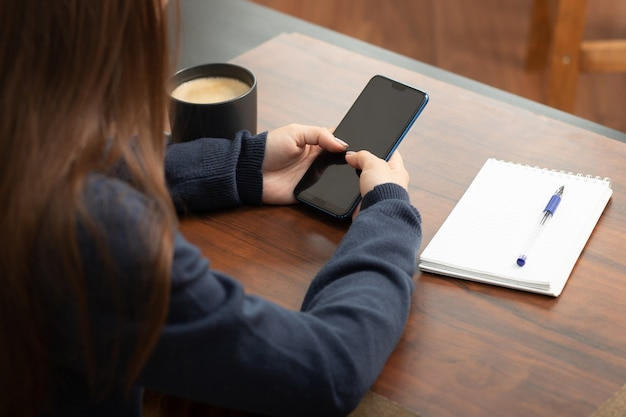 Girl with a smartphone at a table in a cafe communicates in social networks, drinks coffee