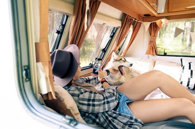 Девушка со смартфоном фотографирует зевающую собаку