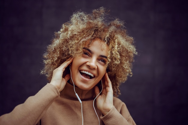 Girl with a smile on her face holding hands on her ears and enjoying music.
