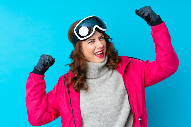 Girl with snow glasses over isolated wall
