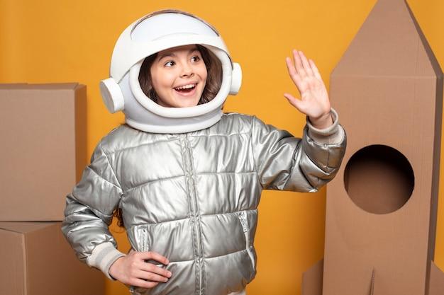 Девушка с космическим шлемом машет