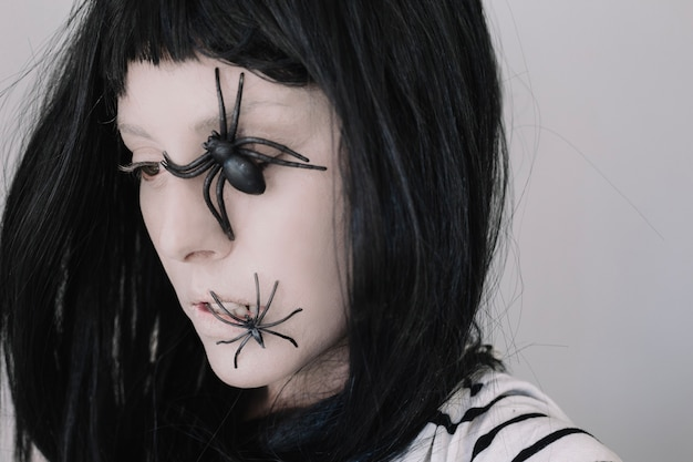 Девушка с пауками на лице, глядя в сторону