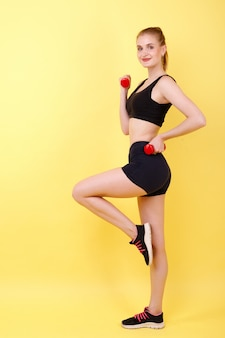 Girl with sports dumbbells on a yellow space