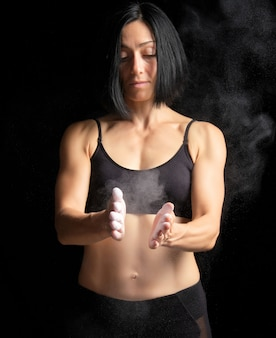 Girl with a sports figure dressed in a black top claps in her hands with white magnesia