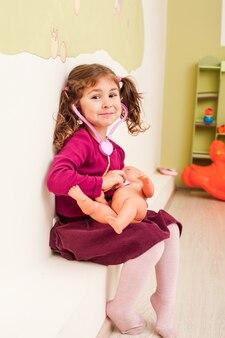聴診器を持った女の子が医者を遊んで人形を聞いています
