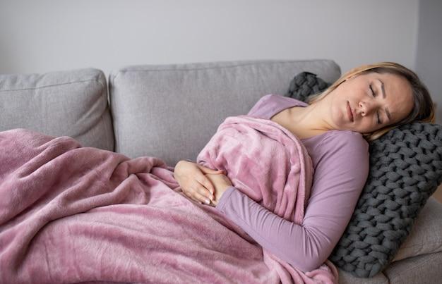ソファーに座っていた胃の痛みを持つ少女
