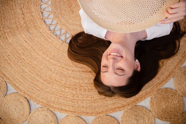 Girl with straw hat dreaming and smiling. girl is dreaming about summer holidays. top horizontal view. health and happiness concept copyspace