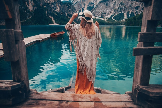 Girl with straw hat on turquoise lake with wooden boats in mountains.