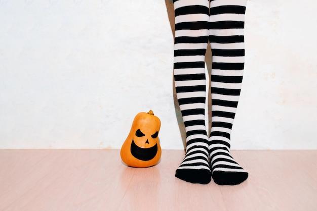 Девушка в полосатых носках рядом с тыквой на хэллоуин