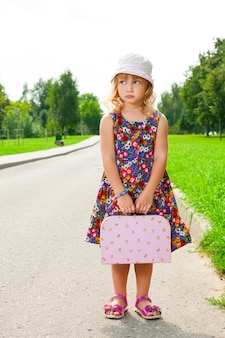 Girl with suitcase standing on road