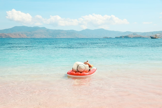 A girl with summer hat laying on inflatable water mattress in pink sandy beach enjoying summer