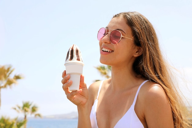 Girl with sunglasses on the beach eating ice cream