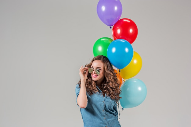 Ragazza con occhiali da sole e mazzo di palloncini colorati