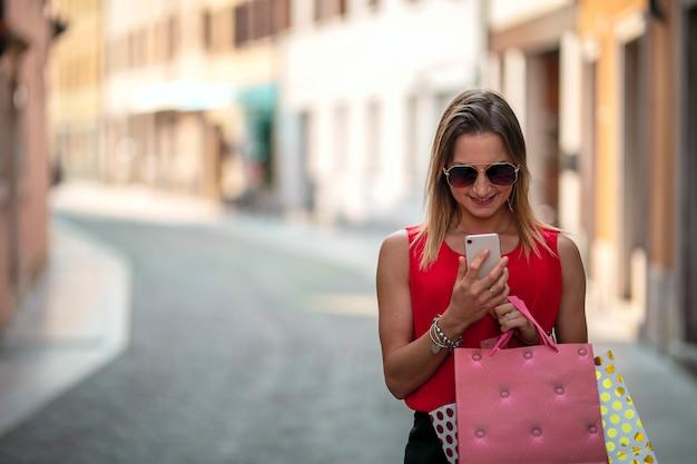 買い物袋と彼女の電話を保持しているサングラスを持つ少女