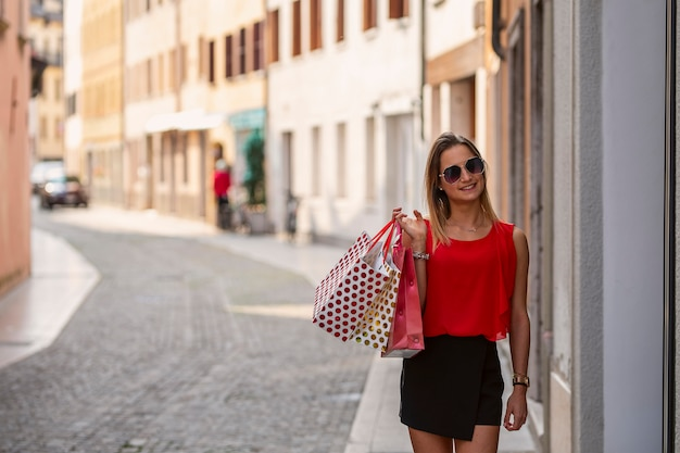 買い物袋を保持しているサングラスを持つ少女
