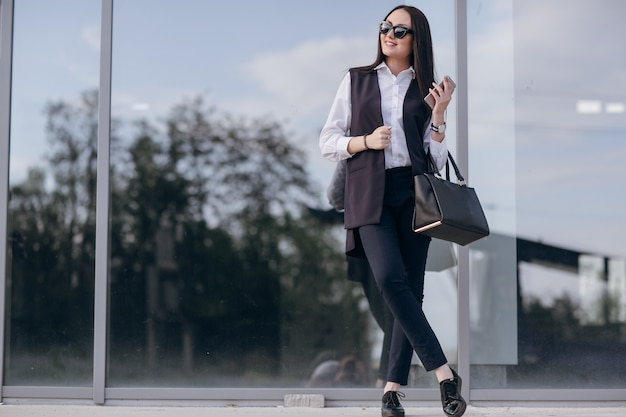 Girl with sunglasses leaning on a dark glass with a bag